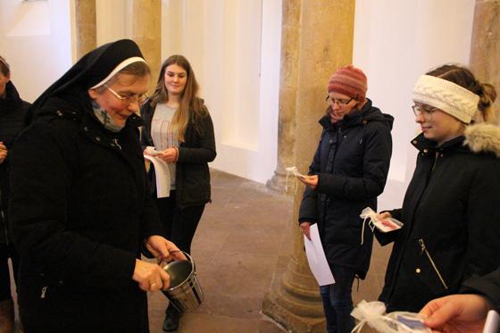 Eine Ordensschwester segnet mit Weihwasser die jungen Menschen